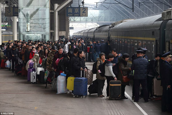 People wait in line to board a train at Nanjing railway station today as millions of people try to make their way home for holiday