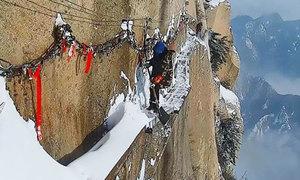 Công nhân dọn tuyết trên vách núi đá dựng đứng cao gần 700 m