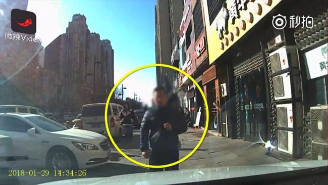 Người đàn ông đi bộ giữa vỉa hè cảm thấy bực tức vì bị bấm còi đòi nhường đường cho xe đi.