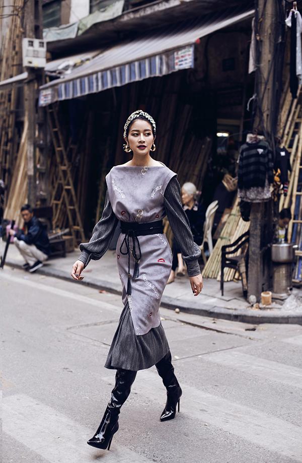 Màu xám của mùa đông Hà Nội và boots dài overknee mang đến cảm giác ấm áp. Hoạ tiết thêu gợi không khí của Tết truyền thống trong tổng thể khá đương đại của bộ trang phục.