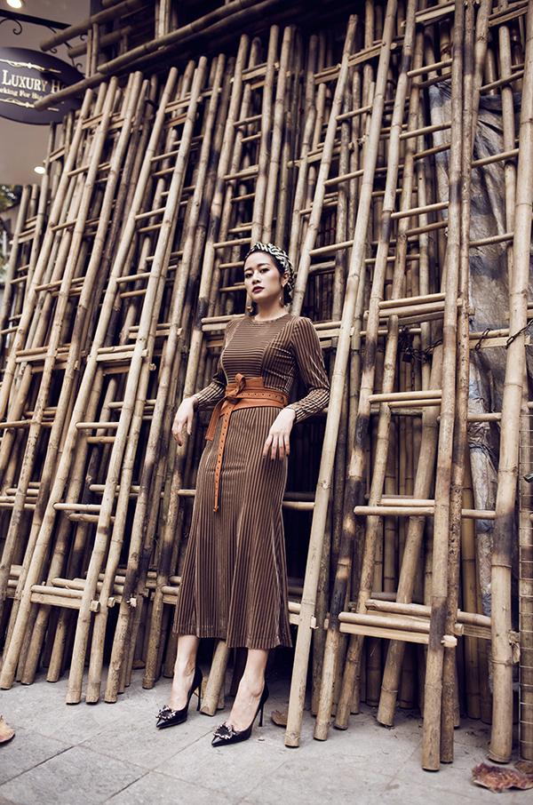 Váy nhung dáng dài cổ điển kết hợp cùng thắt lưng bản to màu nổi bật và turban cùng tone. Các màu sắc trên cùng một dải màu luôn có thể kết hợp với nhau, như ở đây là nâu và cam đất.