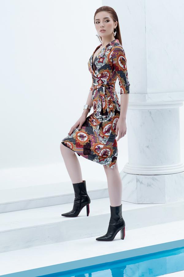 Váy cổ vest trang trí vạt quấn trở nên bắt mắt hơn với họa tiết trìu tượng đan xen những tôn màu nóng phù hợp không khí xuân hè.