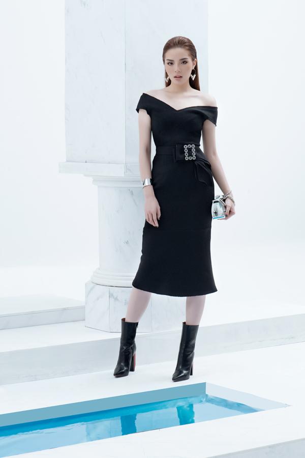 Váy trễ vai tông đen được thêm những điểm nhấn bắt mắt bằng phụ kiện trang trí ánh bạc và clutchchất liệumetalic kích thích thị giác cao.