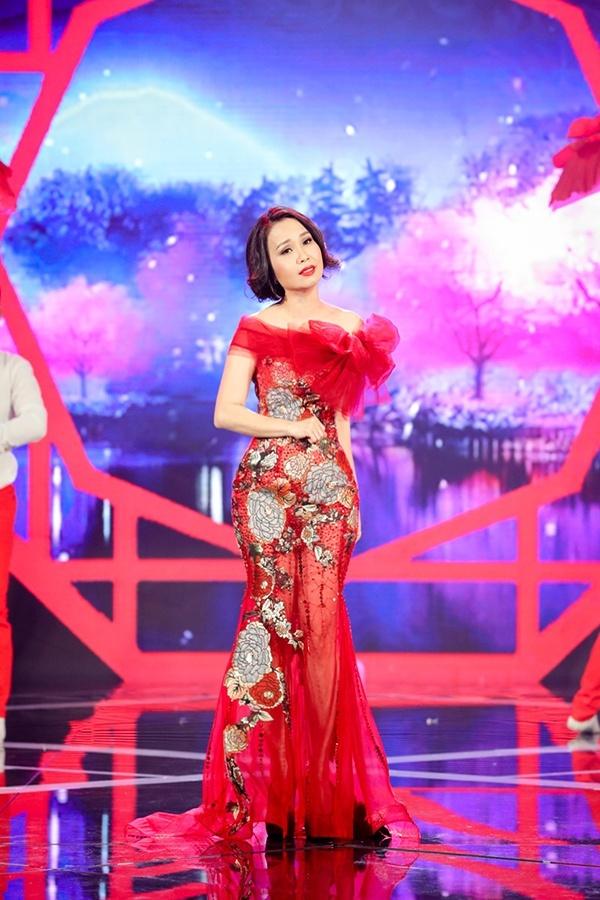Váy dạ hội của ca sĩ Cẩm Ly vốn đã quá nổi bật với tông màu đỏ tươi và họa tiết hoa lá rực sắc xuân, vì thế chi tiết nơ to bản tạo khối 3D trở nên dư thừa và khiến tổng thể thêm rối mắt.