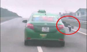 Cảnh sát nằm trên capo taxi chạy trên cao tốc