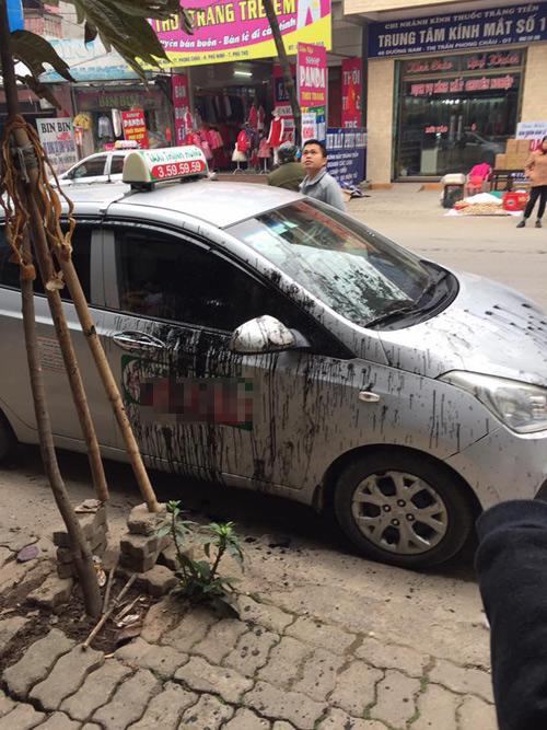 Chiếc xe taxi bị hắt đầy dầu lên thân xe.