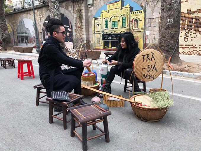 Tùng Dương và Thanh Lam thanh thản dạo bộ ở phố bích hoạ Phùng Hưng. Nam ca sĩ có cơ hội nếm thử trà đá diva do nữ ca sĩ bán.