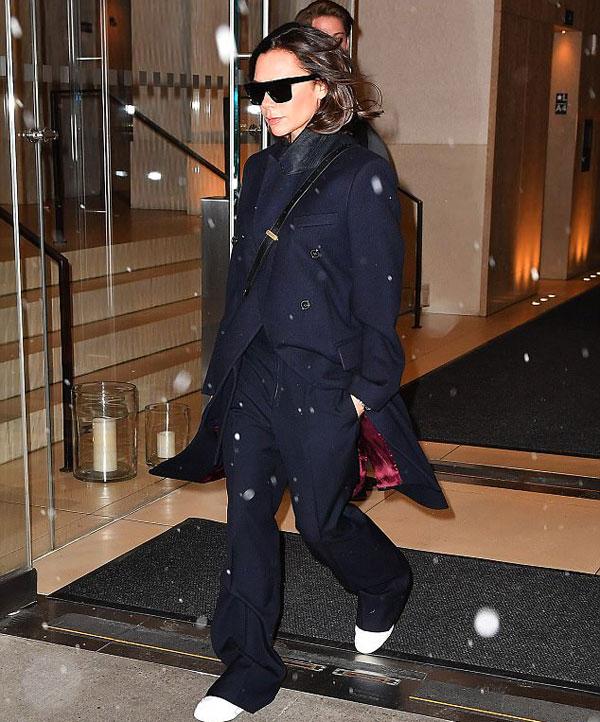 Biểu tượng thời trang vẫn giữ phong thái lạnh lùng quen thuộc, lăng xê mẫu thiết kế của bản thân. Vic cũng từ bỏ giày cao gót, đi đôi giày đế thấp tiện lợi.