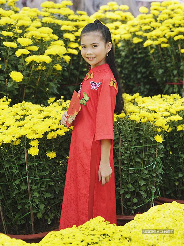 Trang phục truyền thống đỏ thắm giúp bé gái nổi bật giữa vườn cúc đại đoá, loài hoa luôn được người dân phương Nam yêu thích và chọn lựa để trang hoàng nhà cửa trong dịp Tết.