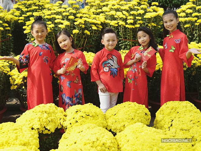 Những mẫu áo dài đỏ tươi với hoạ tiết hoa bướm muôn màu được lựa chọn cho các nhóc tỳ chưng diện khi đi dạo phố hoa xuân.