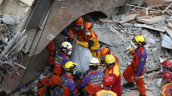 Nhân viên cứu hộ đưa thi thể cặp vợ chồng ra khỏi đống đổ nát tòa nhà Yun Men Tsu Ti. Ảnh: SCMP