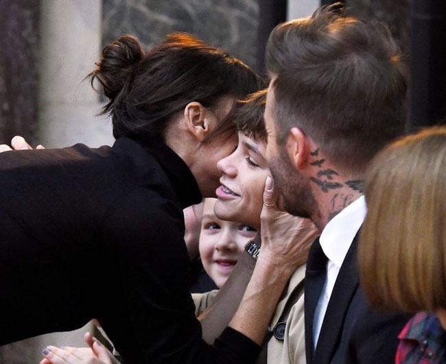 Sau khi ôm hôn chồng, Vic ôm và hôn một lượt các con. Trong ảnh, cựu ca sĩ nhạc pop hôn má cậu hai Romeo.