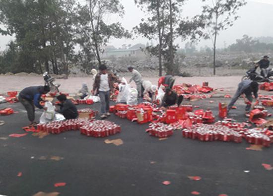 Người dân kéo nhau ra giúp đỡ chủ xe thu nhặt các lon nước ngọt vào bao tải.