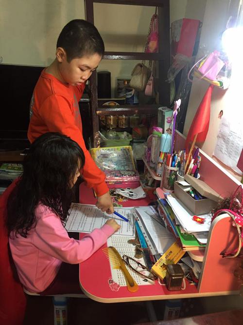 Ngoài việc nhà, Khánh còn giúp mẹ dạy em học.