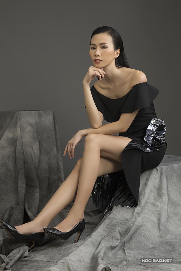 Váy trễ vai tông đen trở nên cuốn hút hơn khi được trang trí bèo nhún điệu đà và phối vải kim tuyến.