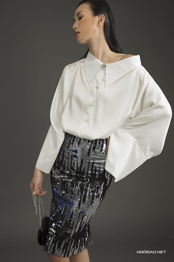 Sơ mi cách điệu tông trắng cùng kiểu túi mini nhỏ xinh đơn giản về màu sắc sẽ dung hoà cho tổng thể khi mẫu váy phối hợp được làm bằng vải sáng chiếu lấp lánh.