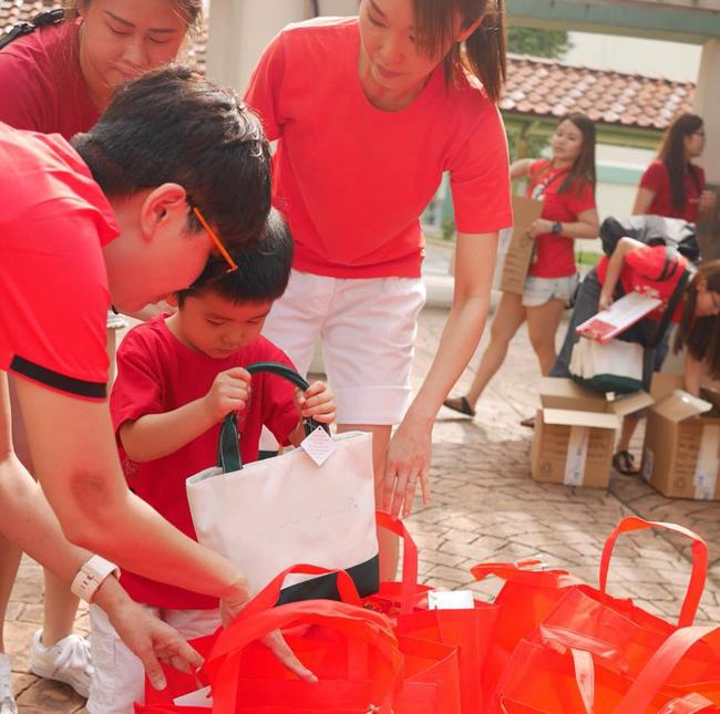 Bé Zed tự mình xếp quà vào túi, dưới sự trợ giúp của các cô, chú trong đoàn tình nguyện.
