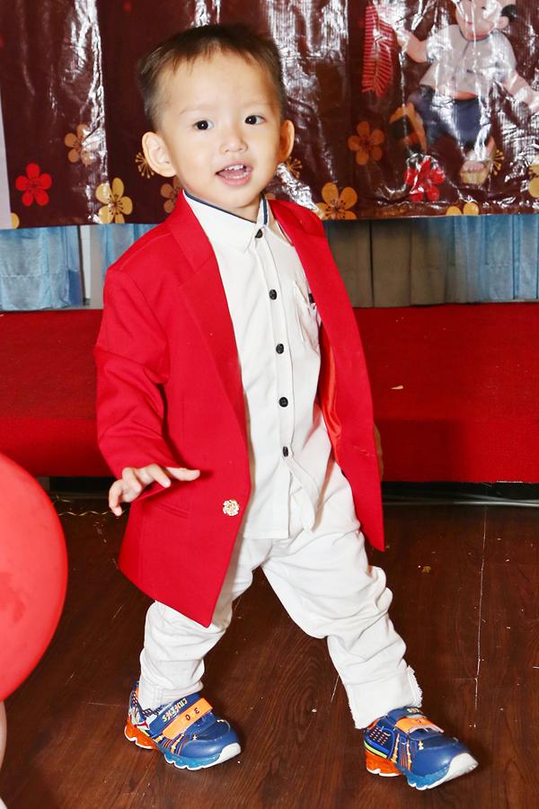 Bé Tấn Đức thay hai trang phục trong buổi tiệc. Cậu bé tỏ ra hiếu động, chạy nhảy không ngừng.