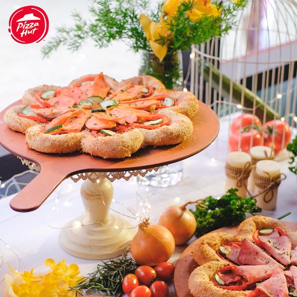 Không chỉ đẹp về hình thức, pizza hoa xuân còn là sự kết hợp hài hòa hương vị ẩm thực Đông  Tây. Vỏ bánh độ mềm xốp đúng chuẩn và thơm vị phô mai. Phần nhân cá hồi bùi bùi, beo béo được nêm đậm đà rất hợp khẩu vị người Việt.