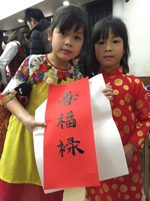 Các cháu bé xúng xính trong trang phục truyền thống, khoe chữ được ôngđồ tặng.