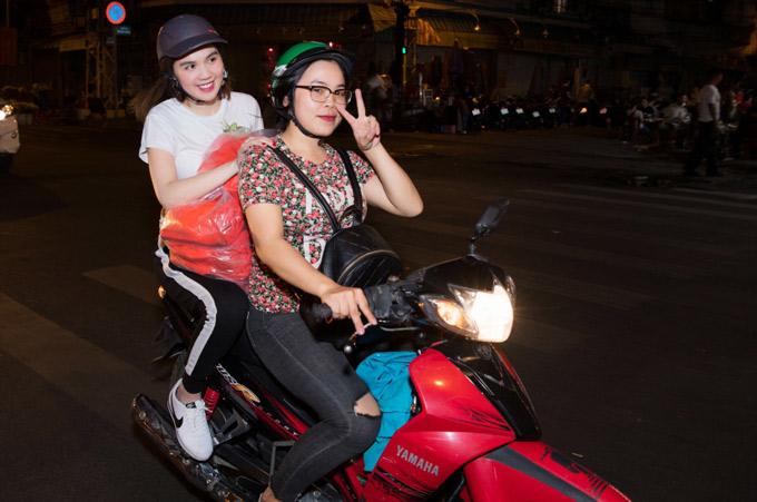 Ngọc Trinh mặc trang phục thể thao đơn giản, ngồi sau xe máy một cô bạn thân.