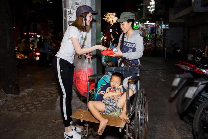 Người phụ nữ bán vé số rất mừng khi được nữ người mẫu lì xì sớm trong đêm giao thừa.