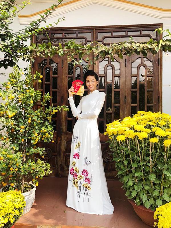 Hoa hậu Hoàn vũ Việt Nam 2017 duyên dáng trong bộ áo dài trắng thêu hoa sen của nhà thiết kế Thuận Việt. HHen Niê về Buôn Mê Thuột từ vài ngày trước để cùng gia đình chuẩn bị đón Tết.