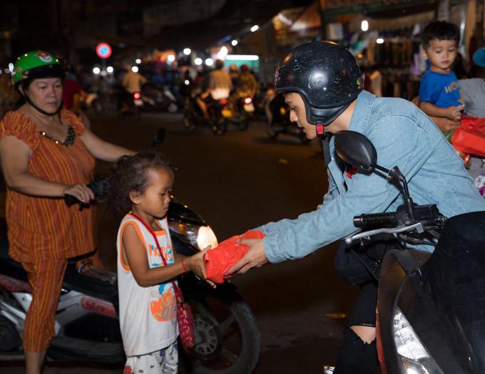 Lâm Vinh Hải ân cần tặng quà Tết cho một em nhỏ lang thang xin ăn trên đường.