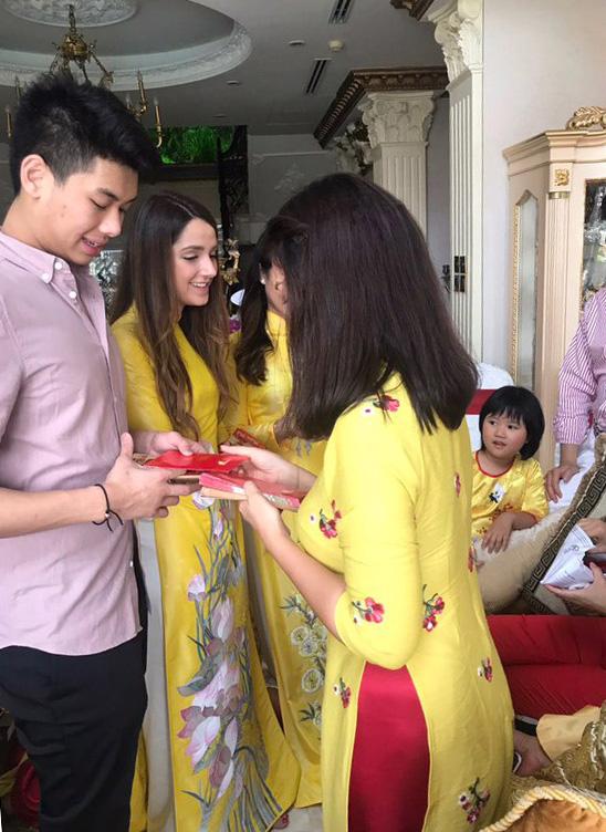 Cậu ấm Hiếu Nguyễn - em út trong gia đình - ăn mặc giản dị, lễ phép nhận bao lì xì từ chị gái.