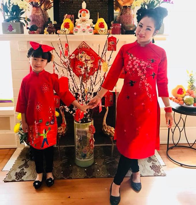 Thuý Nga đón Tết ở Mỹ cùng con gái. Hai mẹ con nữ diễn viên mặc áo dài truyền thống xúng xính chụp ảnh bên cành đào - đặc trưng của ngày Tết quê hương.
