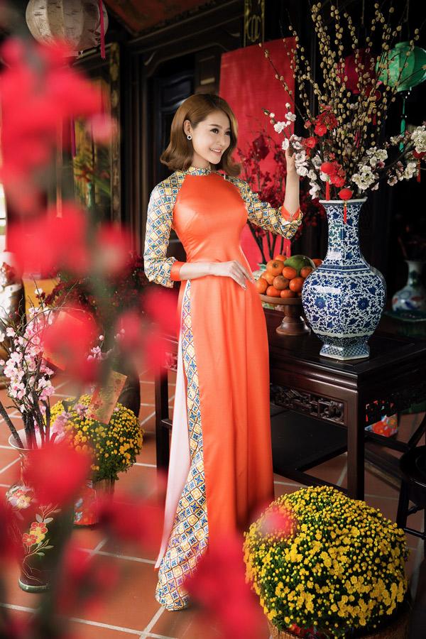 Linh Chi điệu đà với trang phục truyền thống, tạo dáng trong không gian đầy sắc xuân.