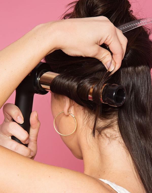 Sau khi xịt một lớp dưỡng tóc, cuộn tóc vào máy uốn xoăn theo chiều từ trong ra ngoài.