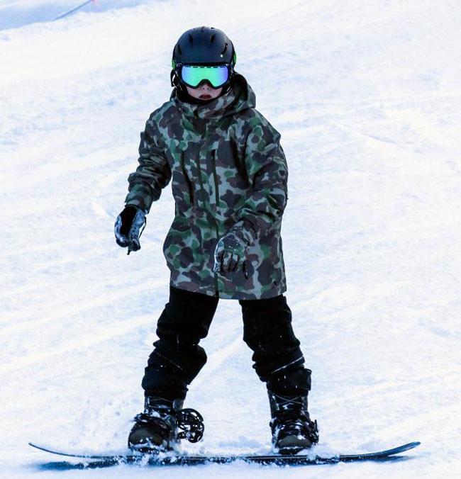 Nhóc Cruz chọn chiếc áo khoác rằn ri, hào hứng trượt ván tuyết.