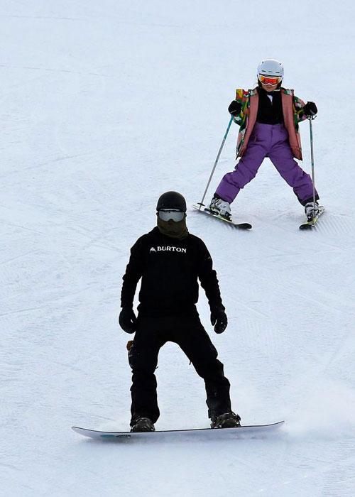 Ông bố 42 tuổi mặc kín mít trượt ván tuyết phía trước con gái.