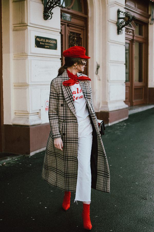 Gam đỏ trở nên đắt giá khi được lựa chọn làm điểm nhấn cho set đồ với mũ baker boy, khăn skinny, bốt mũi nhọn đi với áo choàng kẻ ca rô, jean và áo thun trắng.