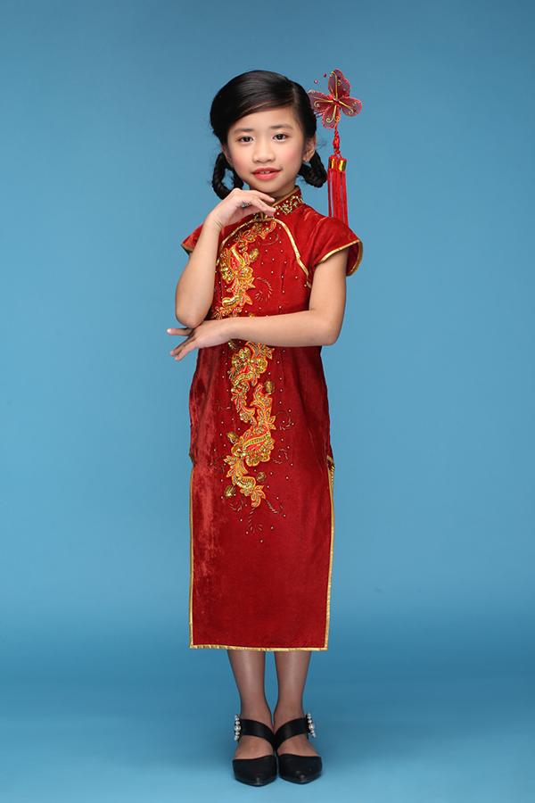 Mẫu áo sườn xám tông màu đỏ tươi mang đặc trưng không khí lễ hội của người Hoa cũng được chọn cho bé Nguyễn Phúc Mi Lan.