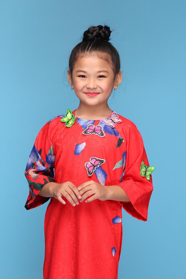 Đặng Lê Mỹ Phương diện áo dài đỏ tươi đi kèm hoạ tiết cánh bướm mùa xuân khi chụp ảnh quảng bá cho sự kiện thời trang thiếu nhi.