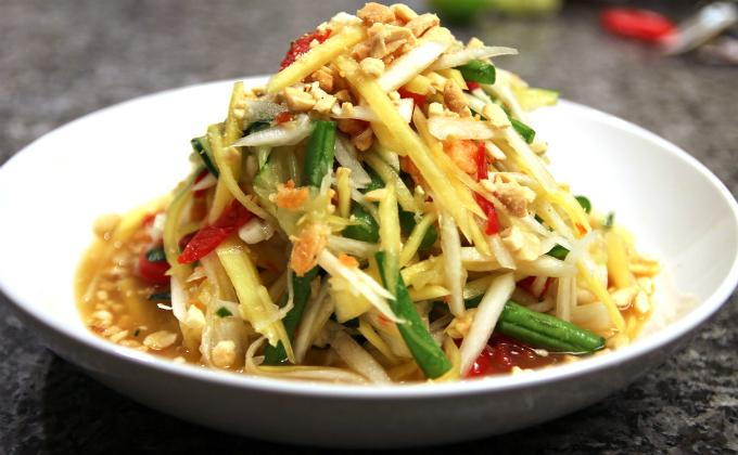 Gỏi đu đủ som tam đã quá quen thuộc với những người mê ẩm thực Thái trên toàn thế giới. Món ăn chỉ bao gồm đu đủ xanh, xoài, dưa chuột, bắp chuối, đậu đũa... cùng lạc gĩa nhỏ cùng nước sốt chua cay đặc trưng nhưng lại ngon tới mức chỉ nghĩ đến cũng ứa nước miếng.