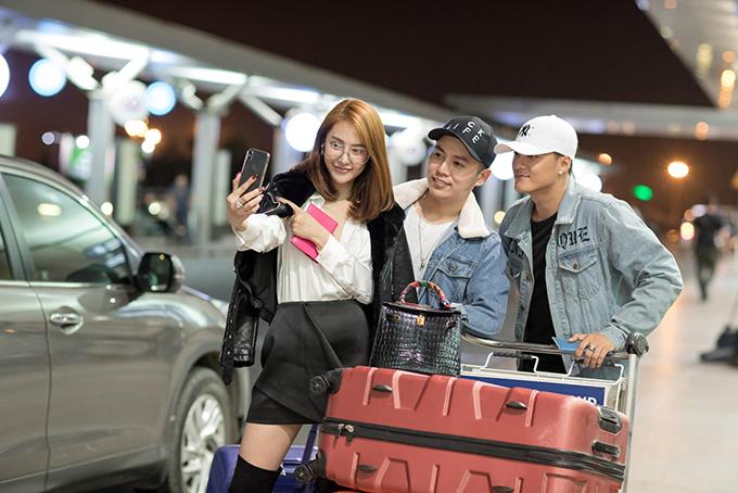 Cặp đôi cùng người bạn chụp ảnh kỷ niệm ở sân bay.