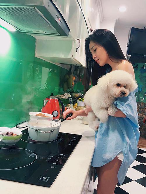 Hiền Thục cũng vào bếp như ai nhưng không quên bế theo chú chó cưng đang nũng nịu.