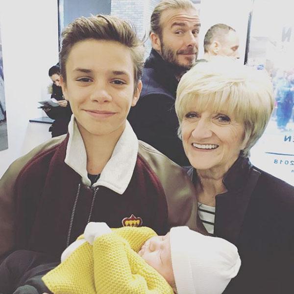 Becks ghé mặt khi con trai Romeo và mẹ đẻ, bà Sandra, bế cô nhóc Peggy.