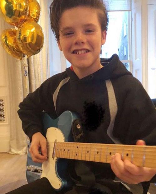 Vic cũng đăng ảnh cậu út cầm cây đàn và khẳng định Cả nhà yêu con rất nhiều trong ngày Cruz tròn 13 tuổi.