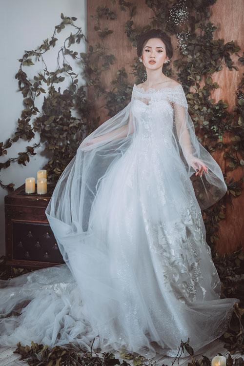 Mẫu váy 2 trong 1 vô cùng tiện lợi để cô dâu có thể nhanh chóng biến hóa phong cách của mình cho buổi tiệc trọng đại. Khi cử hành hôn lễ, cần sự trang nghiêm và sang trọng, bạn mặc thêm chiếc áo ren lưới dáng cape cách điệu. Còn cởi bỏ lớp khoác ngoài, bạn sẽ thật gợi cảm trong mẫu váy chữ A xòe nhẹ cúp ngực trái tim.