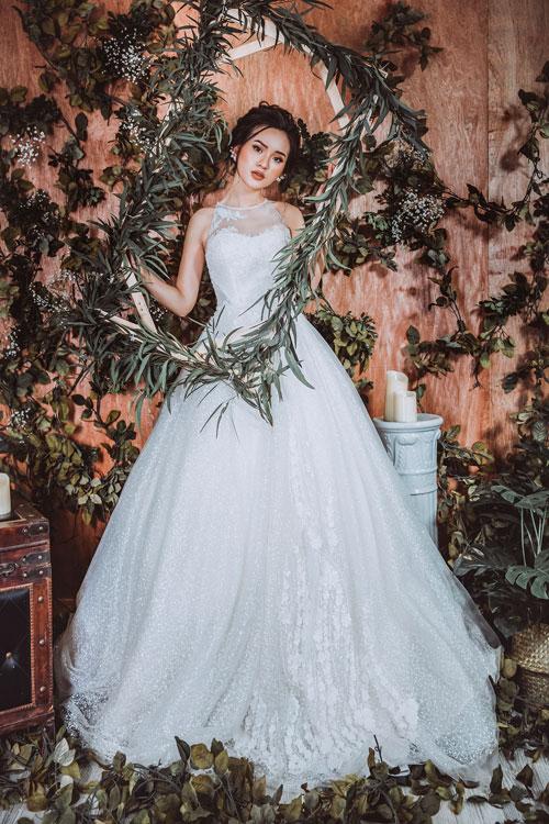 Nếu không tự tin với vòng một của mình, cô dâu có thể chọn mẫu váy cổ yếm chân xòe nhẹ. Điểm nổi bật trongthiết kế này chính là cách kết hợp vải lưới chấm bi với tầng tầng lớp lớp voan, ren mang đặc trưng phong cách của quý cô châu Âu thập niên 90.