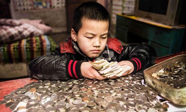 Li Guoliang tiết kiệm được 1.353 tệ từ tiền lẻ và tiền xu để chữa bệnh cho em. Ảnh: SCMP