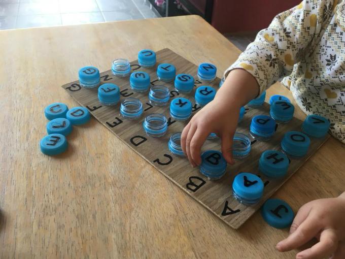 Vừa làm quen với các chữ cái, bé còn được rèn luyện kỹ năng khéo léo khi vặn các nắp vào cổ chai.