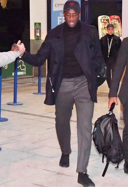 Yaya Toure bắt tay với một trong số ít CĐV ở sân bay Manchester.