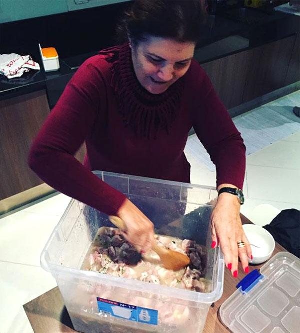 Bà Dolores Aveiro dùng hộp nhựa to chuẩn bị cho món hầm. Ảnh: NS.