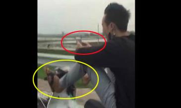 Nam thanh niên vừa lái xe bằng chân vừa nghịch điện thoại