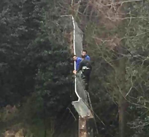 Zhang và người bạn trèo lên hàng rào 3 mbao quanh công viên để trốn vé. Ảnh: Asia Wire